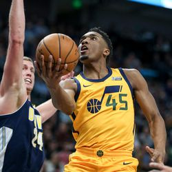Utah Jazz guard Donovan Mitchell (45) lays it up ahead of Denver Nuggets center Mason Plumlee (24) at Vivint Smart Home Arena in Salt Lake City on Tuesday, Nov. 28, 2017.