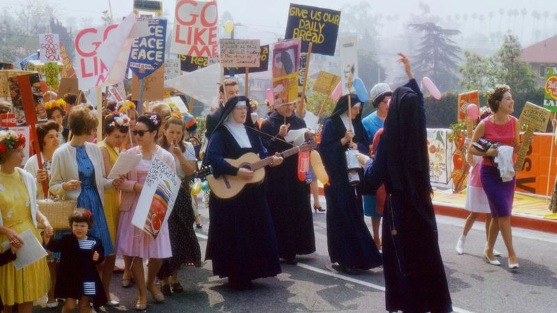 A group of nuns holding protest signs and guitars lead a protest.