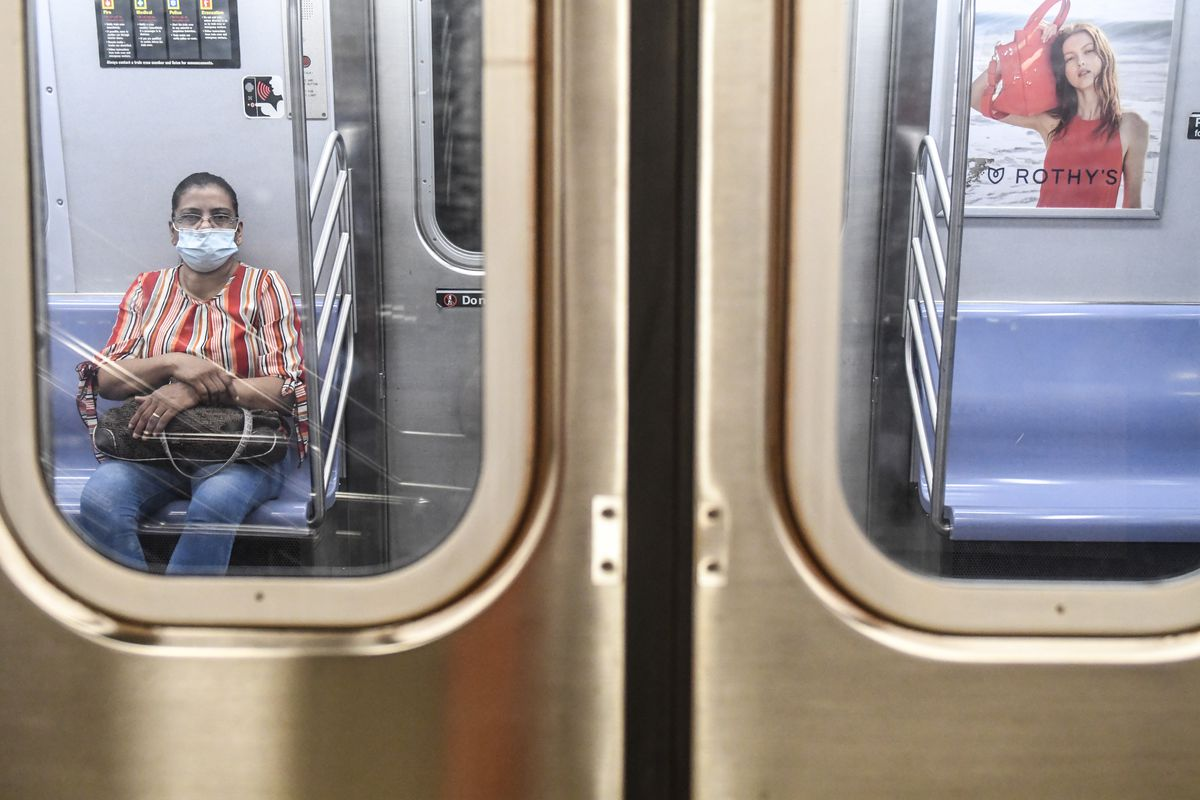 A person wearing a mask commutes on the subway in Brooklyn.