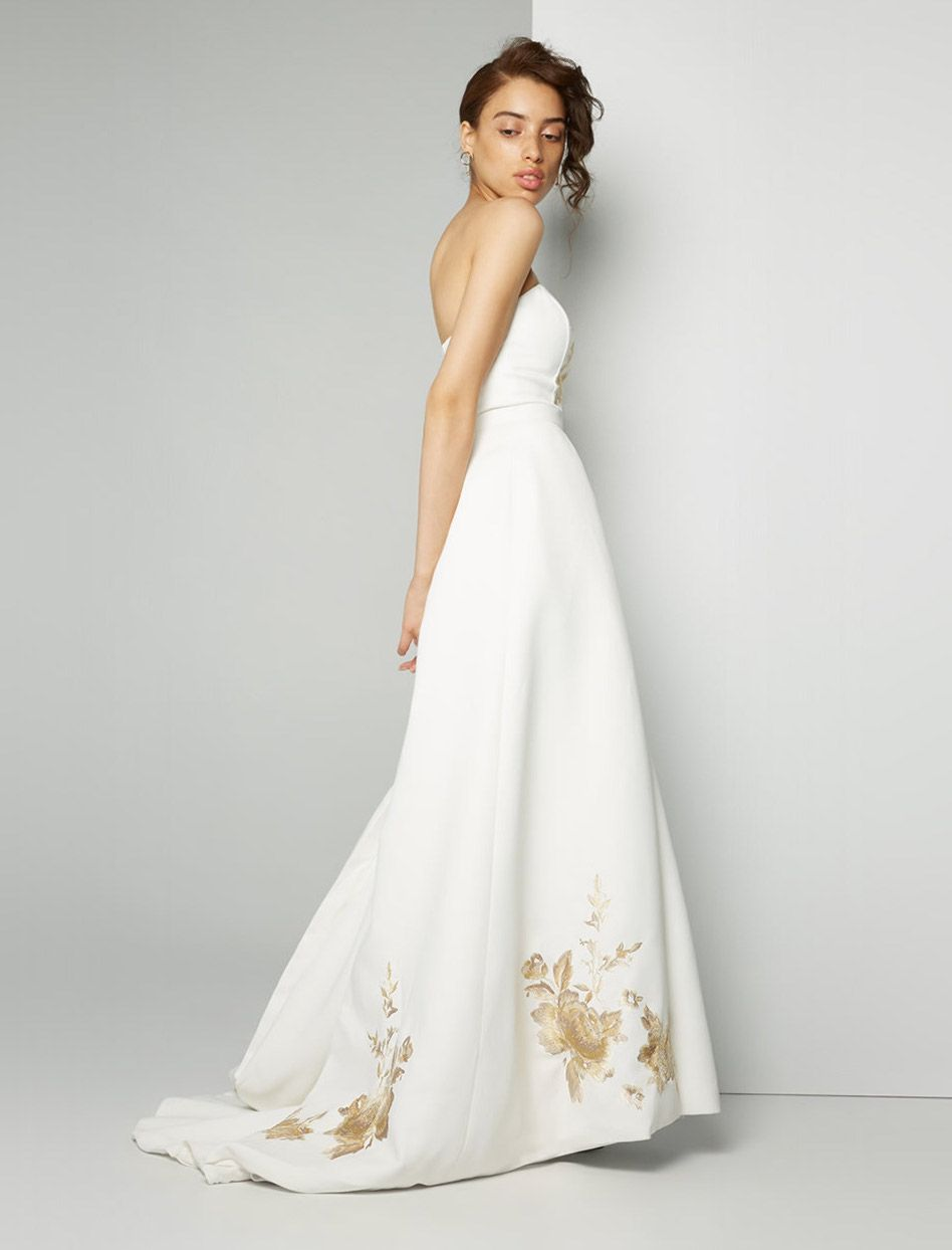4c1ae3233fb A model wearing a white strapless wedding dress with gold embroidery on the  bottom