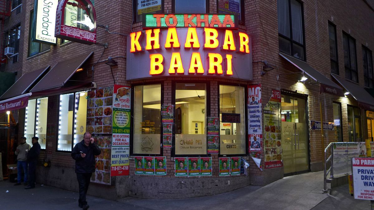 A sign glows yellowish red over big window at the restaurant which is the subject of this story.