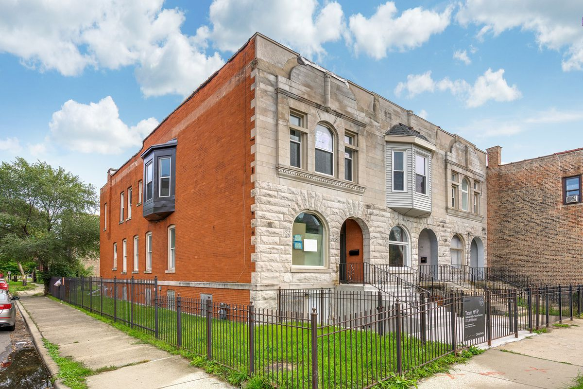 Three row homes with a traditional limestone front facade and brick sides stand on a corner lot surrounded by a dark metal fence.