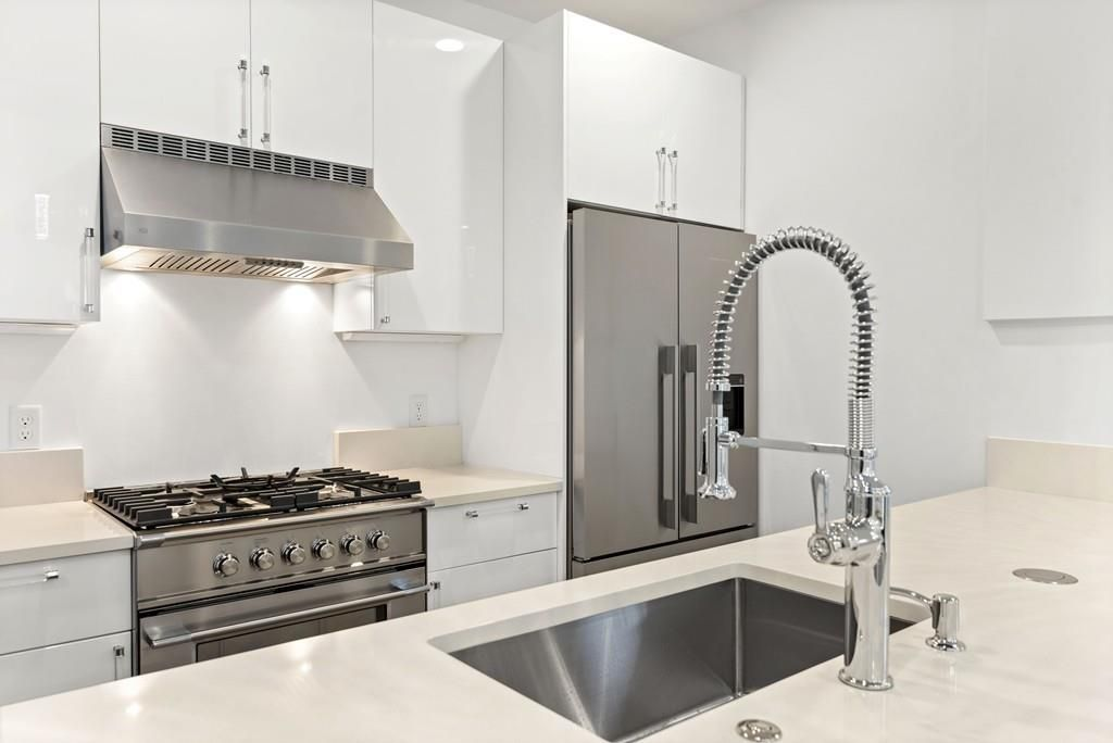 Close-up of a modern kitchen with the faucet in foreground.