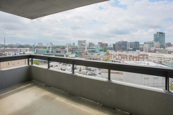 An empty balcony with a city view that includes an open-air ballpark.