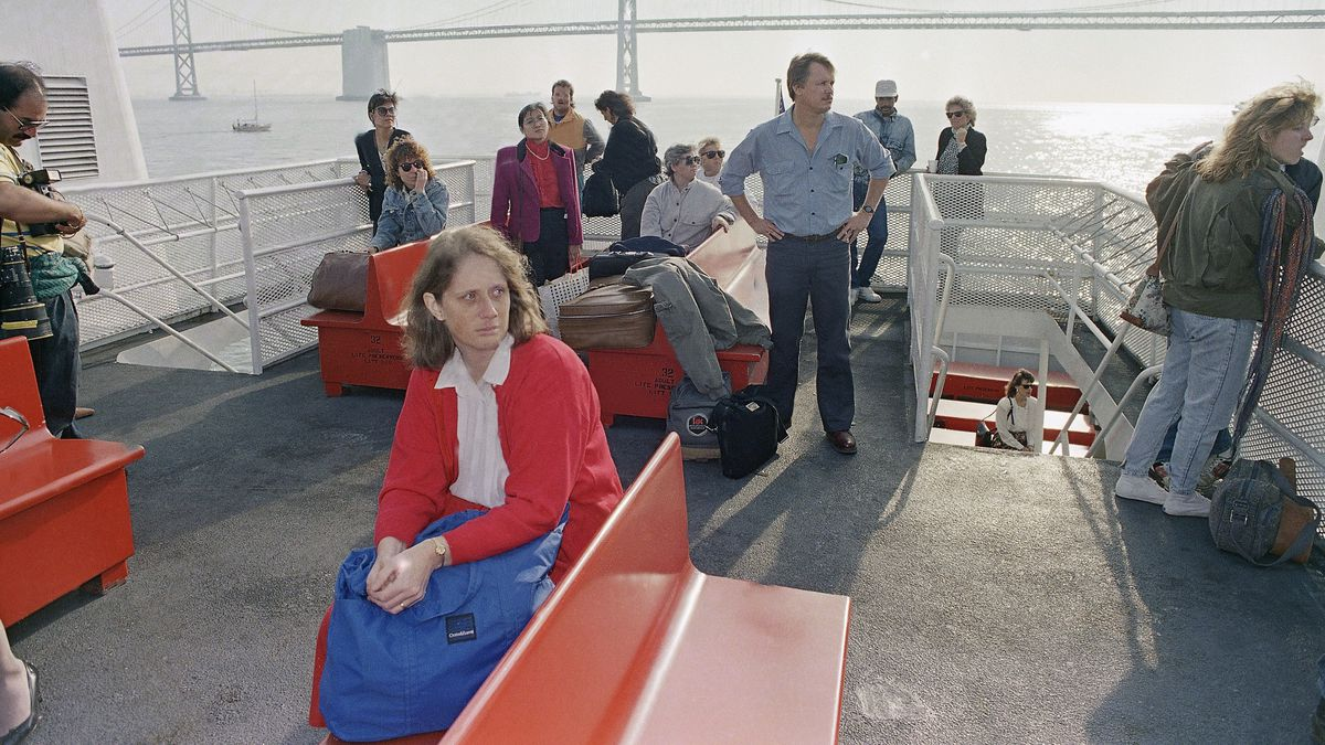 A woman in a red jacket sits on a ferry bench, frazzled and unhappy while other passengers stand in the background.