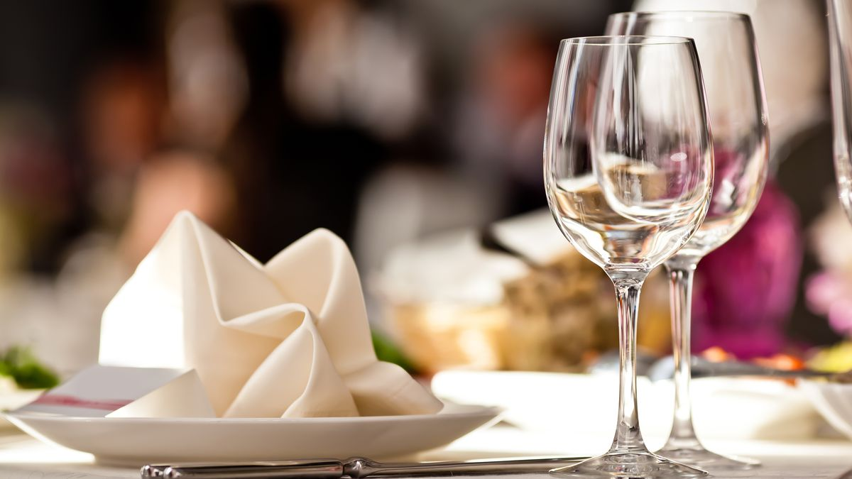 Empty glasses set in restaurant next to a white plate with a white napkin on top on a table with white cloth.
