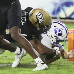 Brigham Young Cougars quarterback Zach Wilson (1) scores on UCF Knights defensive back Jon Powell (34) during the Boca Raton Bowl in Boca Raton, Fla., on Tuesday, Dec. 22, 2020.