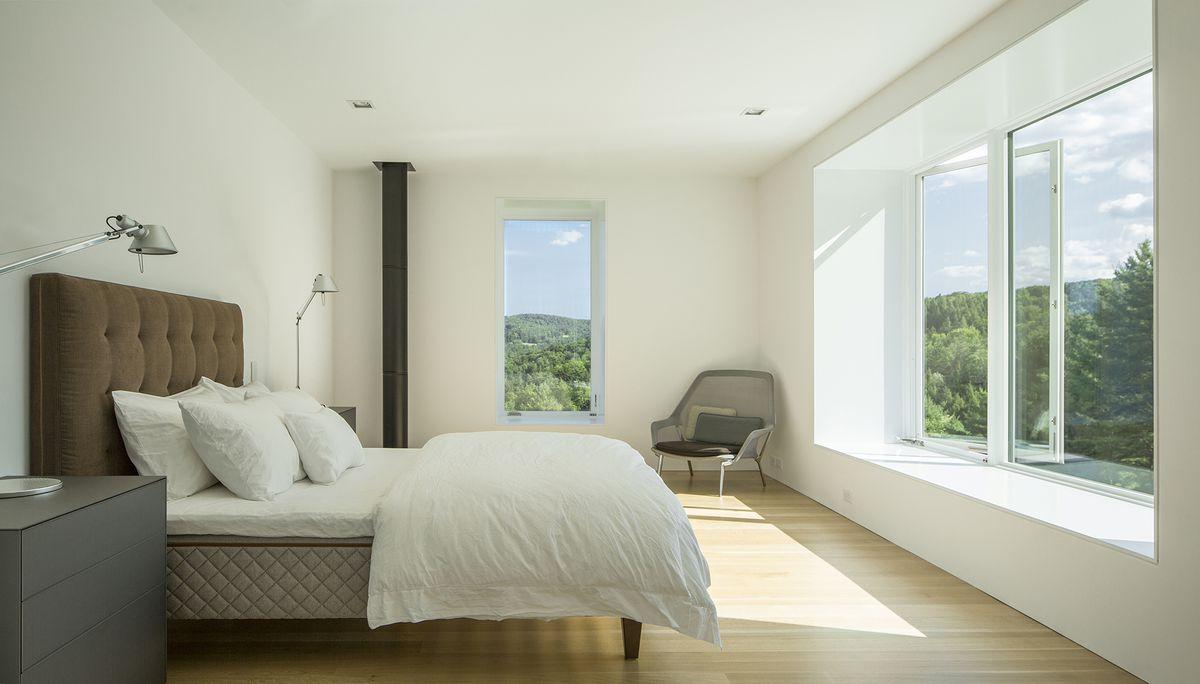 Bed facing large window in bedroom.