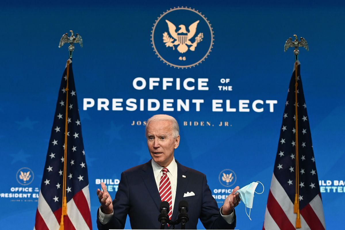 """Biden, in a black suit, white pocket square, and red and white striped tie, speaks into a microphone. Behind him are two US flags and a blue LCD screen with the seal of the president of the US. Under the seal are the words """"Office of the President Elect Joseph R. Biden, Jr."""""""