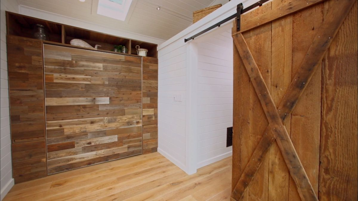 A Murphy bed folded up in a tiny house.