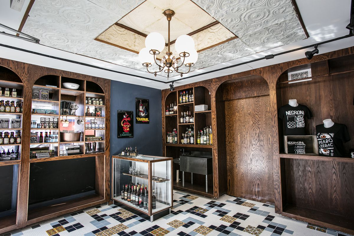 A corner of a retail store with liquor lining wooden cabinets and a tiled floor