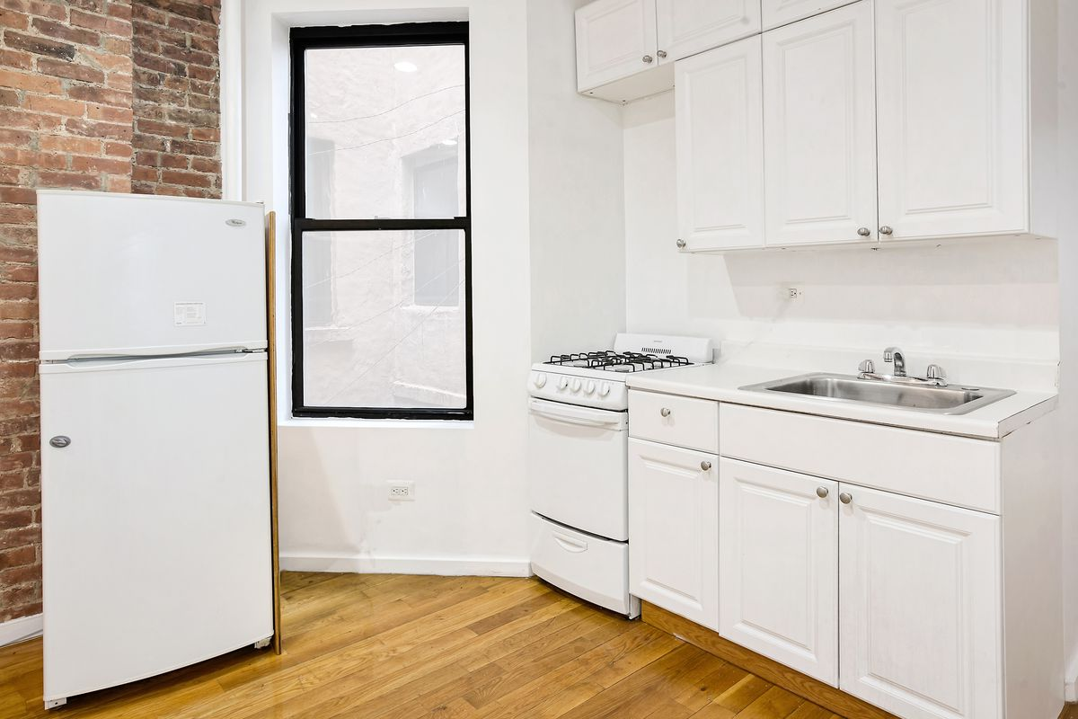 A kitchen with white cabinetry, one window, and a fridge.