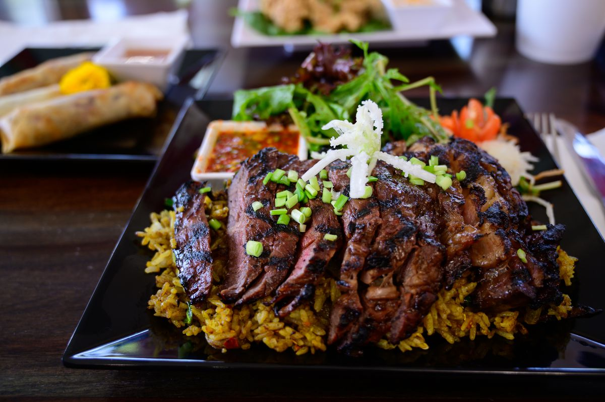 A black plate of sliced steak on top of yellow rice.