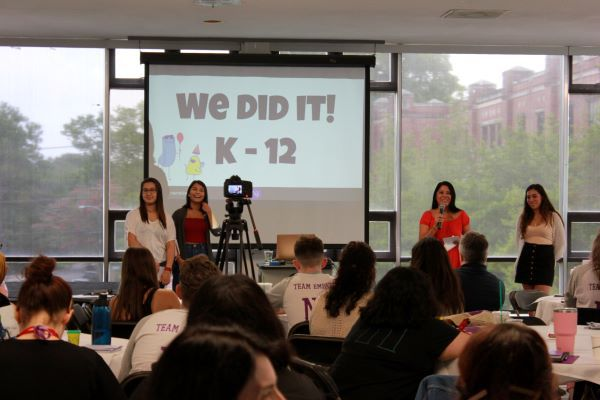 A group of students stand on a stage with a projection on a screen in the background. They participate in Narrative 4's Story Exchange program as other students look on.
