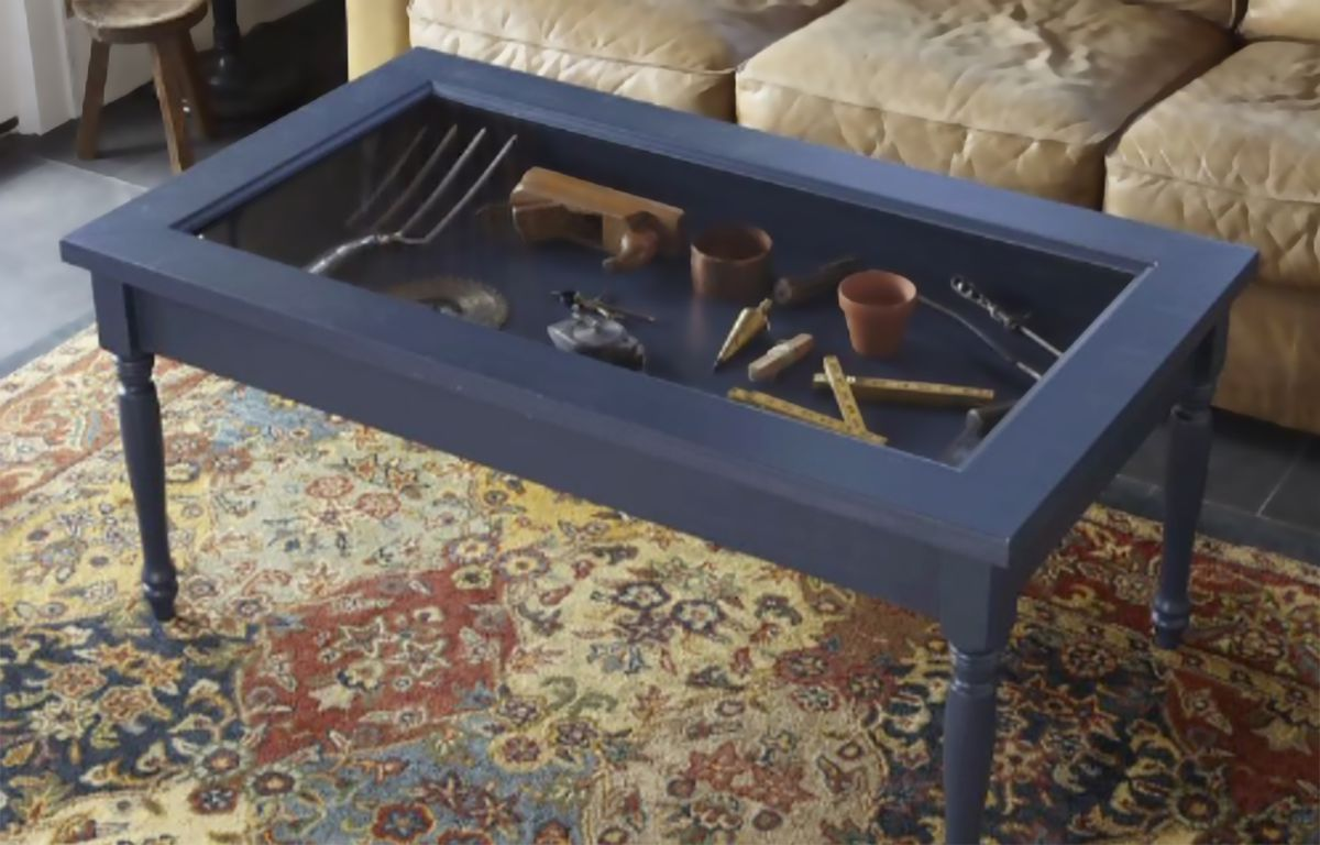 Coffee table with glass display built in revealing gardening tools.