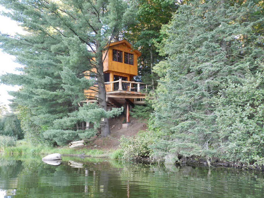 A treehouse on the edge of Walker Pond in Vermont. The treehouse has a wooden facade and is surrounded by trees.