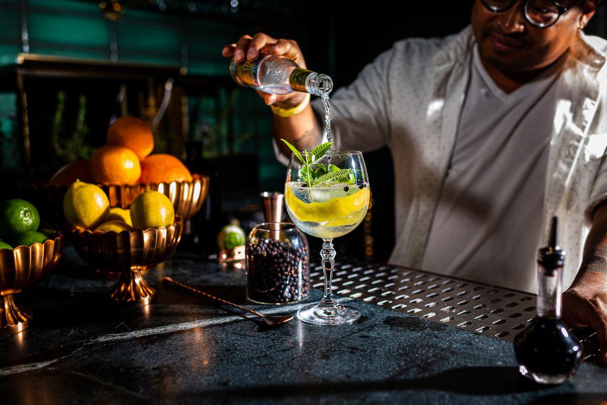 Bar director Philip Keath pours a bottle of tonic into a glass full of gin, lemon verbena, and lemon peel
