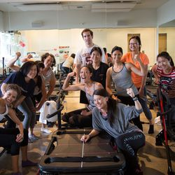 Group two flexes their biceps after conquering the M3 Megaformer machines. That's Jennifer up in the front!