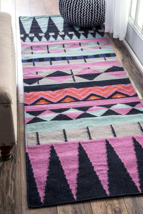 Rug with an angular purple and black pattern.