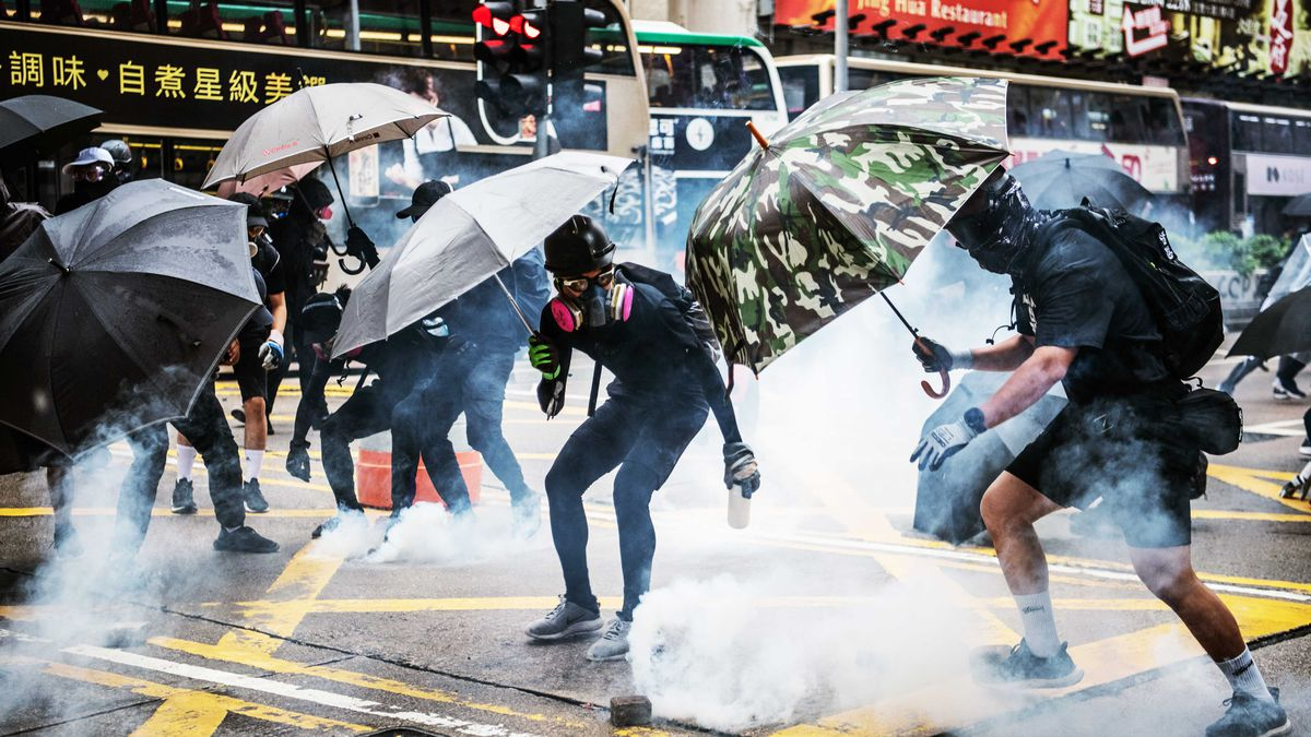 Hong Kong protesters carrying umbrellas dodge tear gas on the street.