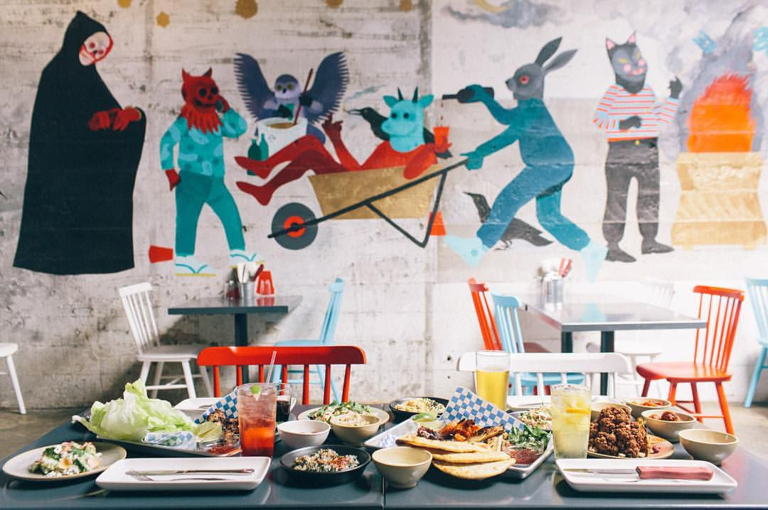 A colorful mural in front of a table filled with food at Georgetown's Bar Ciudad.