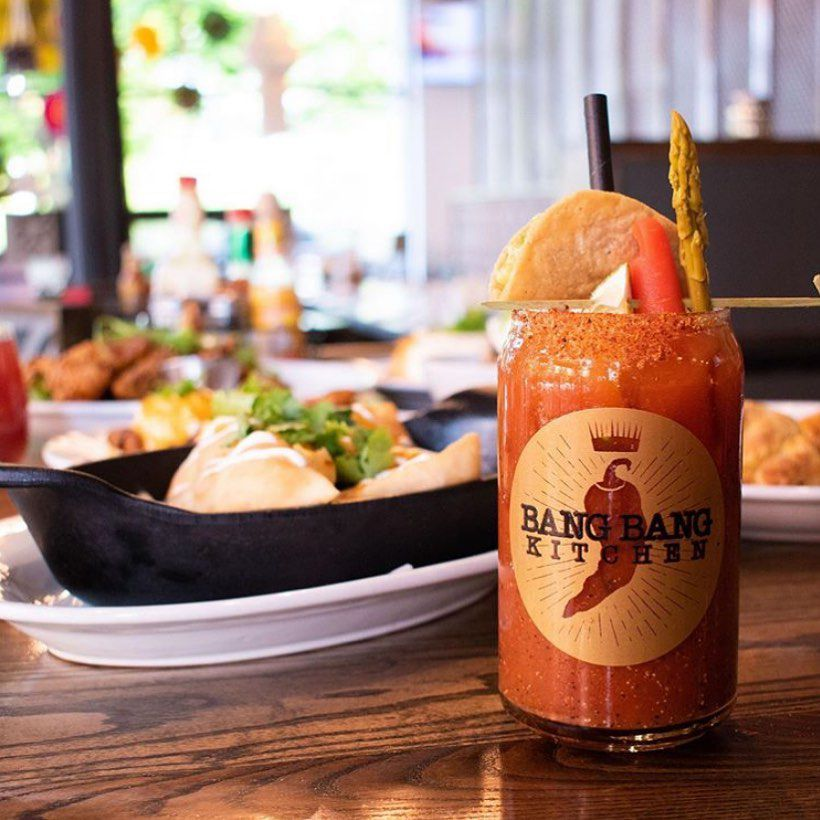 A jar of bloody mary with Bang Bang Kitchen's logo, garnished with asparagus and lemon.