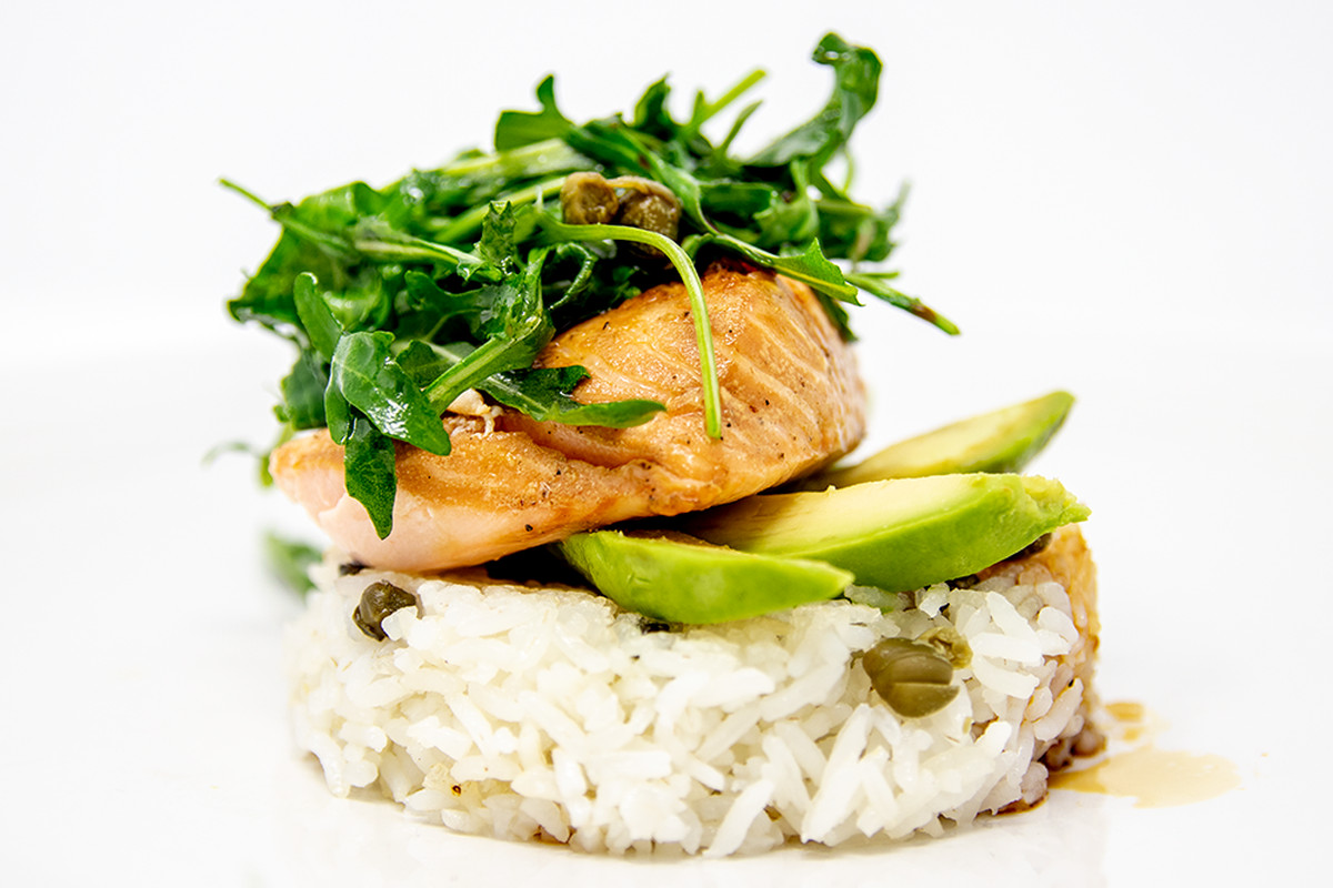 Soy salmon rice cake topped with greens and avocado