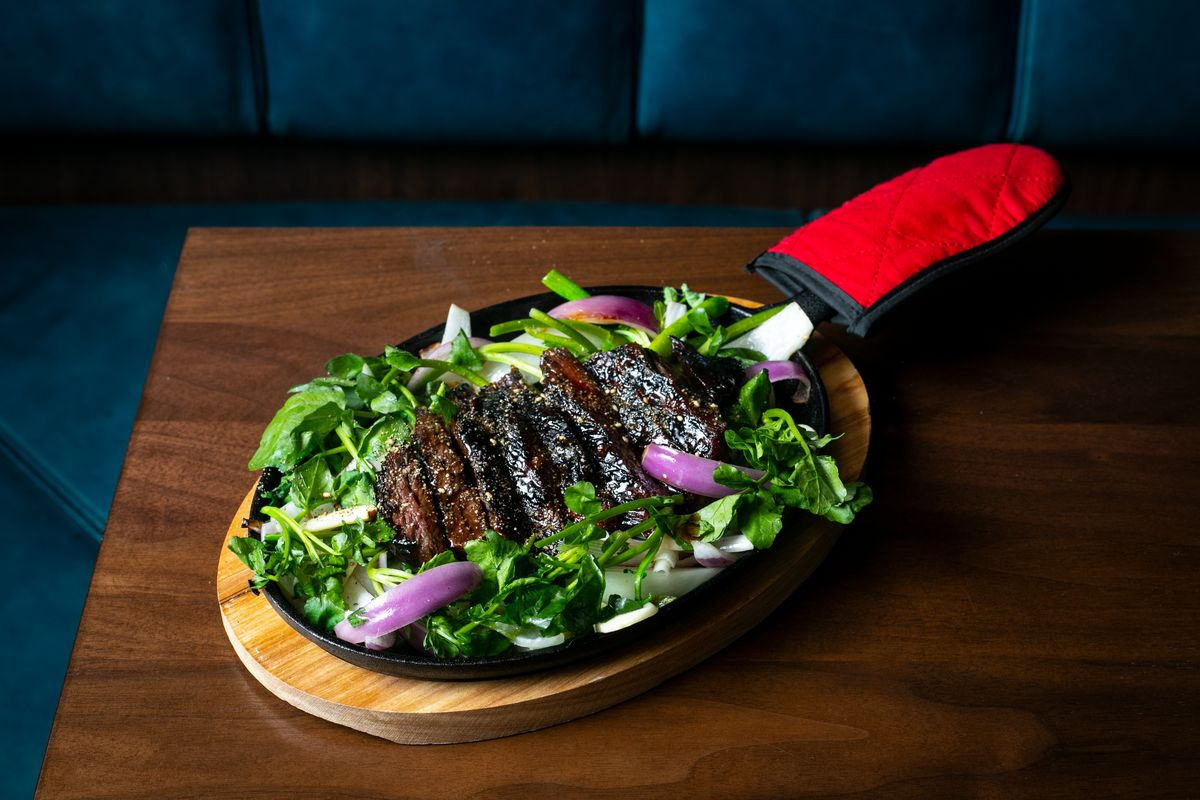 Slices of steak nestled in green leafy lettuces and slices of red onion set in a black pan on a wooden table