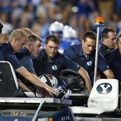 BYU football trainer Jeff Hurst, fifth from left, talks to student assistant Samantha Burton, far right, as she prepares to drive a cart carrying Cougar running back Jamaal Williams to an ambulance after Williams suffered a concussion Sept. 21 during a game against Utah in Provo.