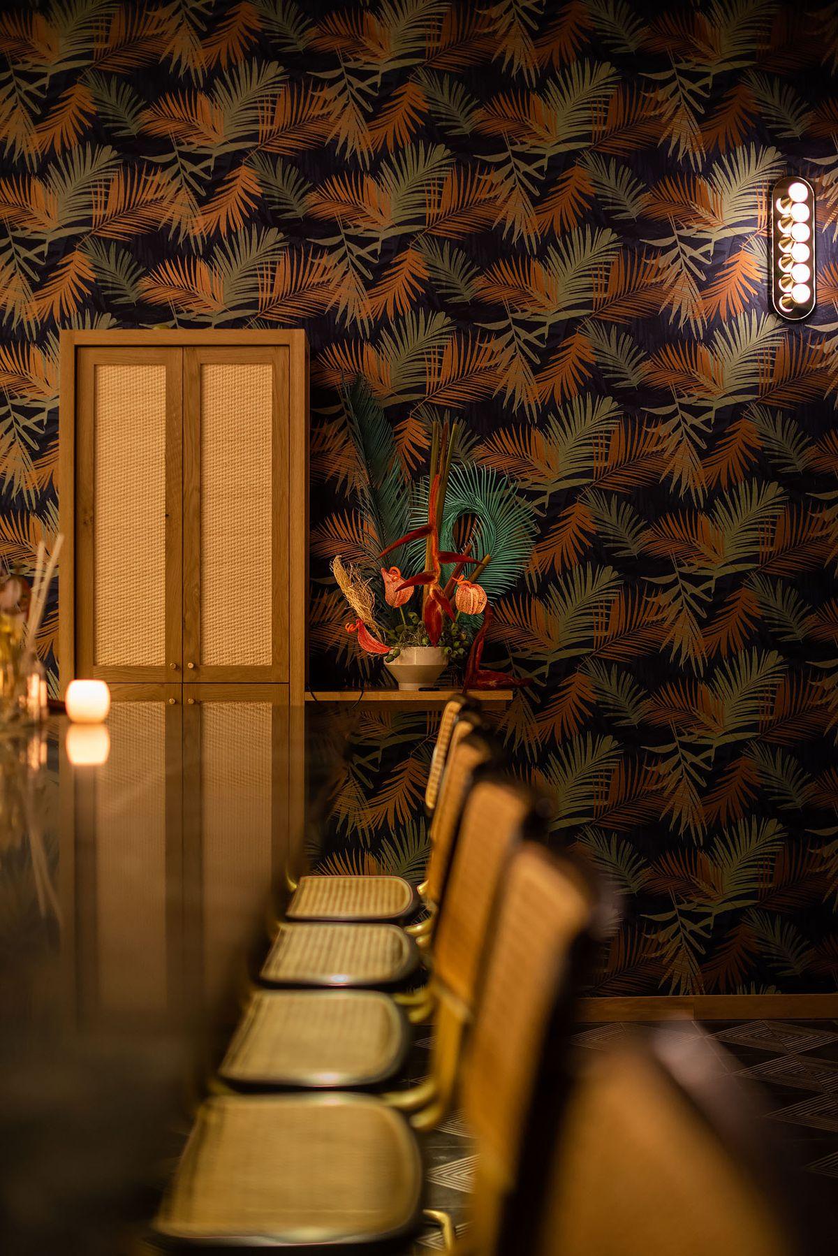 Leafy wallpaper and sconces hang at a moody bar.