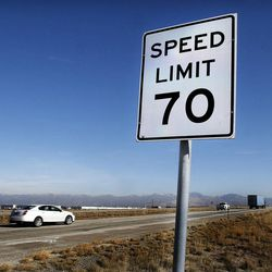 Traffic rolls by after UDOT changes a 65 mph sign to 70 mph on I-80 west of Salt Lake City, Monday, Dec. 8, 2014.