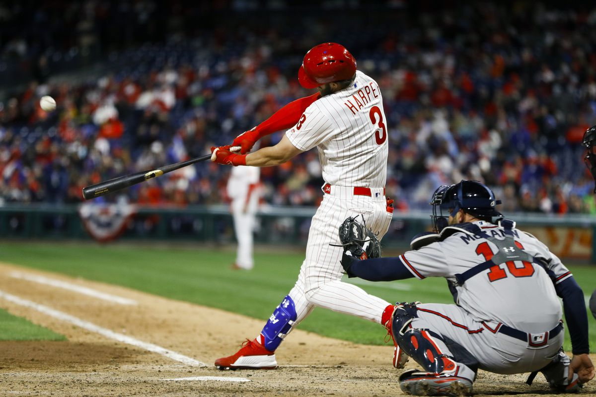 Philadelphia Phillies' Bryce Harper, left, hits a homerun off Atlanta Braves relief pitcher Shane Carle during the seventh inning of a baseball game, Sunday, March 31, 2019, in Philadelphia. At right is catcher Brian McCann. (AP Photo/Matt Slocum)