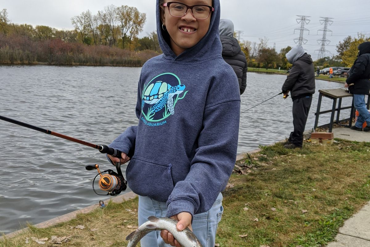 Faith Lofton enjoys a moment with a rainbow trout she caught Saturday at Wolf Lake. Credit: Dale Bowman