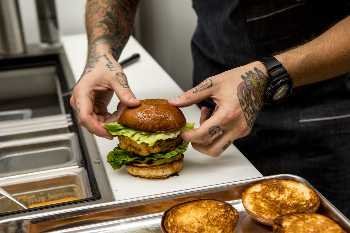 Two hands put a top bun onto a fried chicken sandwich from inside of a bright kitchen.