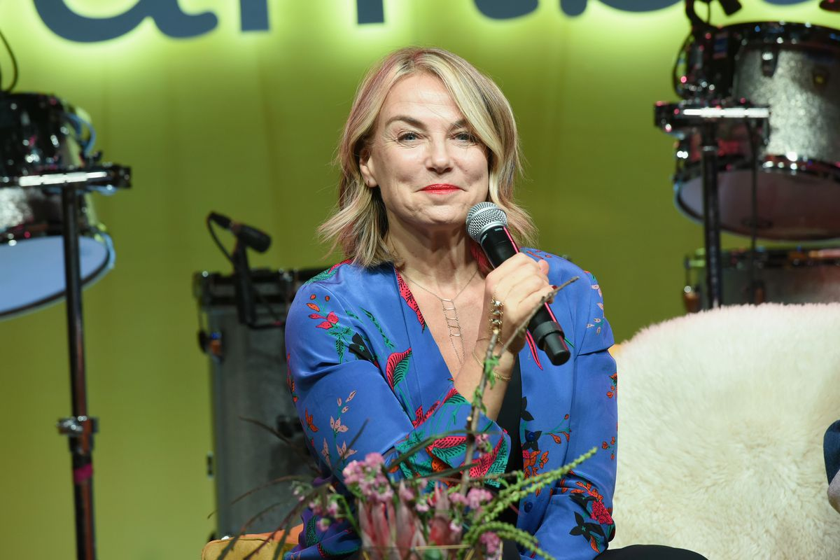 Therapist Esther Perel holds a microphone onstage at SXSW.