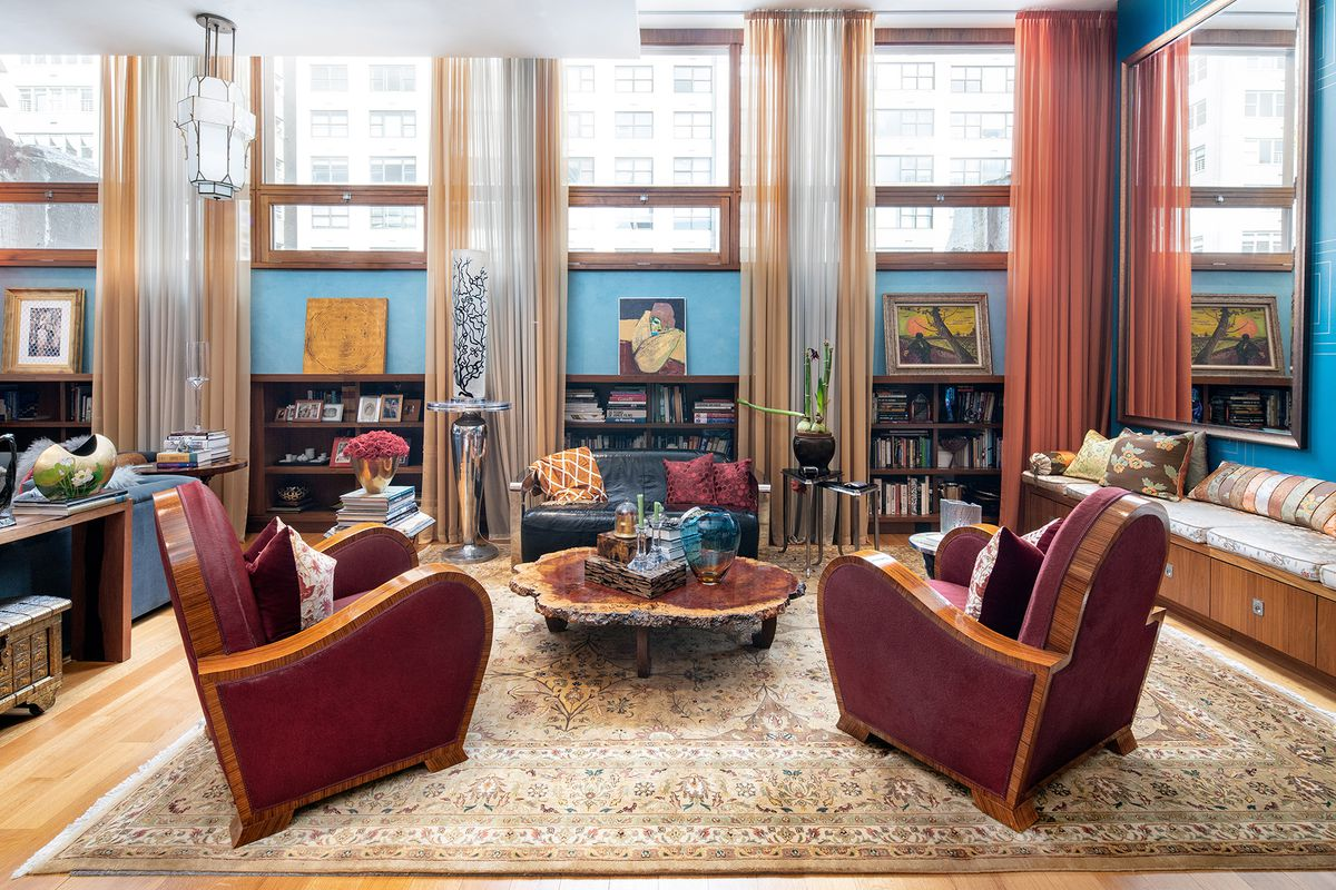 A living room with two red couches, a small black leather couch, a rug, blue walls, and walnut-framed windows.