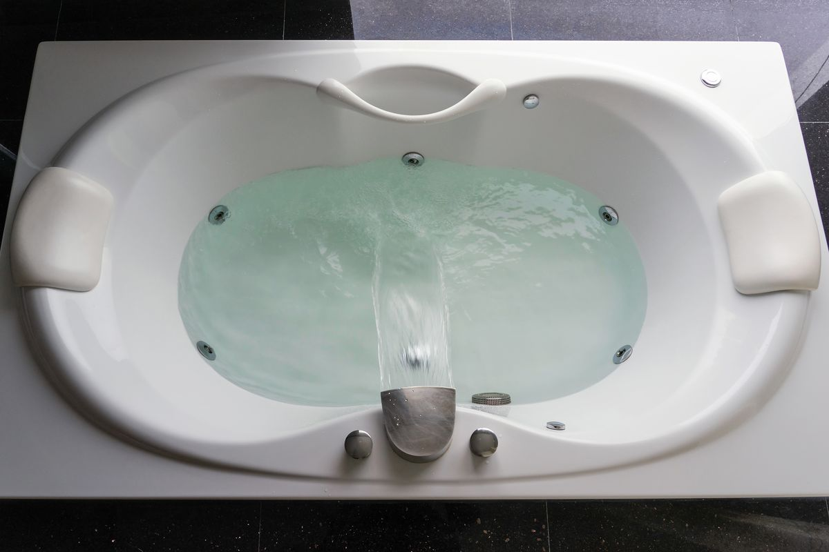 Jetted tub surrounded by black tile.