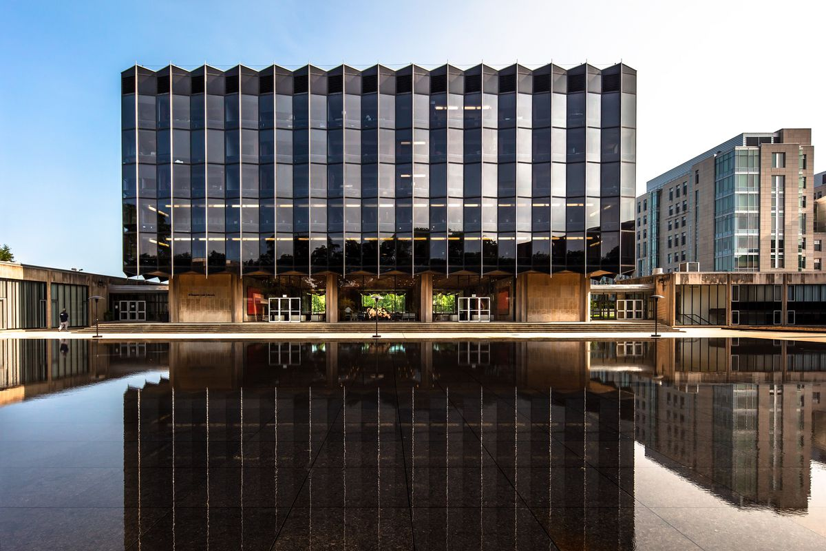 A dark modern building with an angular facade stands before a smooth reflecting pool.