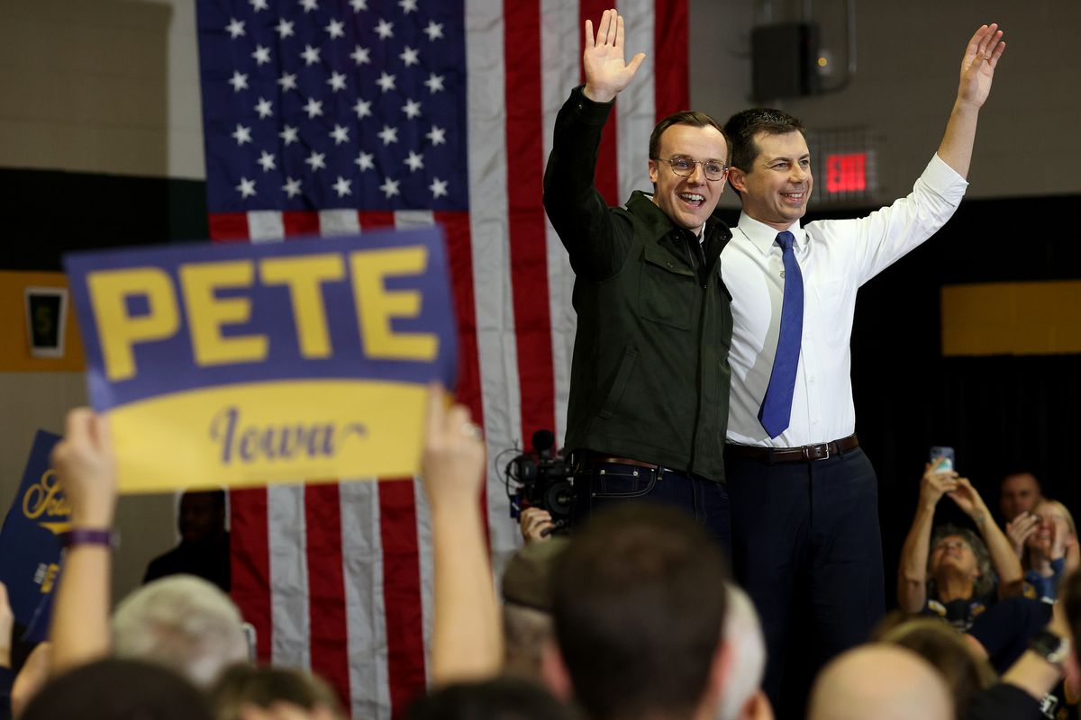 Pete and Chasten Buttigieg wave to the crowd amid supporters holding up signs.