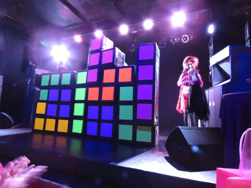 A performer in a bouffant wig stands at a microphone onstage next to oversized Tetris pieces (blocks in various shapes made out of four squares nested together).