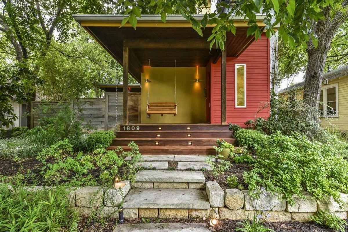 wooden house set back from street, red, yellow, brown exterior, garden beds, big trees