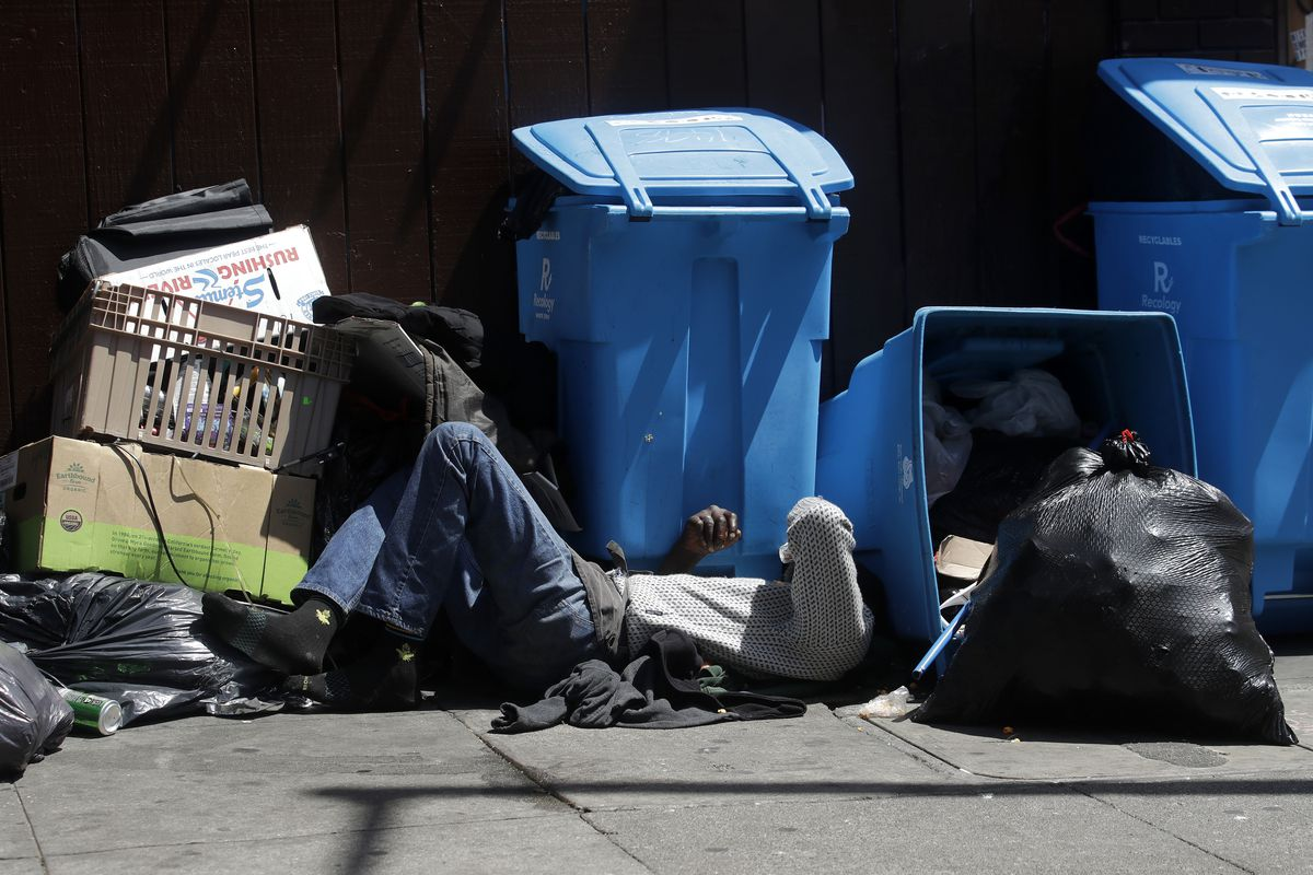 A blue recycling bin and a full black garbage bag on a sidewalk with a man sleeping next to them as he shields his eyes from the sun.