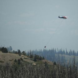 A helicopter drops water as the Brian Head Fire continues to burn in southern Utah on Friday, June 30, 2017. The evacuation order for Brian Head and Dry Lakes was lifted Friday, 13 days after residents were forced from their homes by the raging fire.