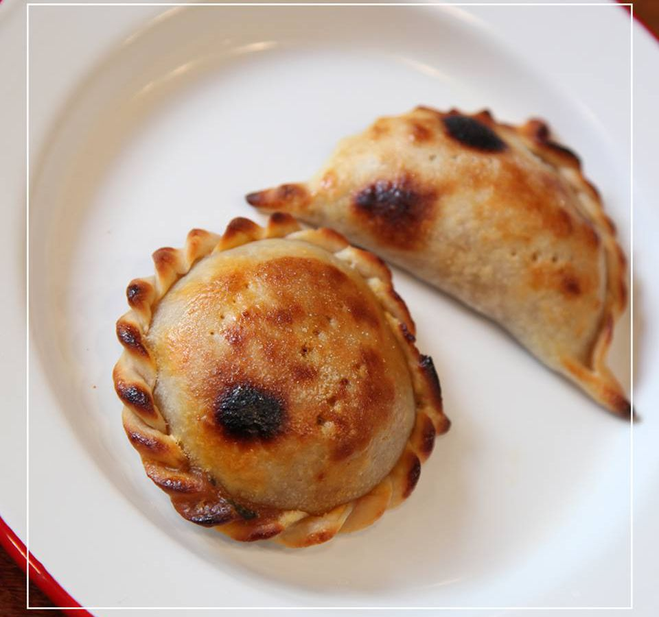 As seen from above, a plate with two empanadas crispy from the oven, one upright and one on its side.