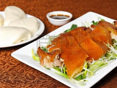 A plate of duck served with baos and sauce.