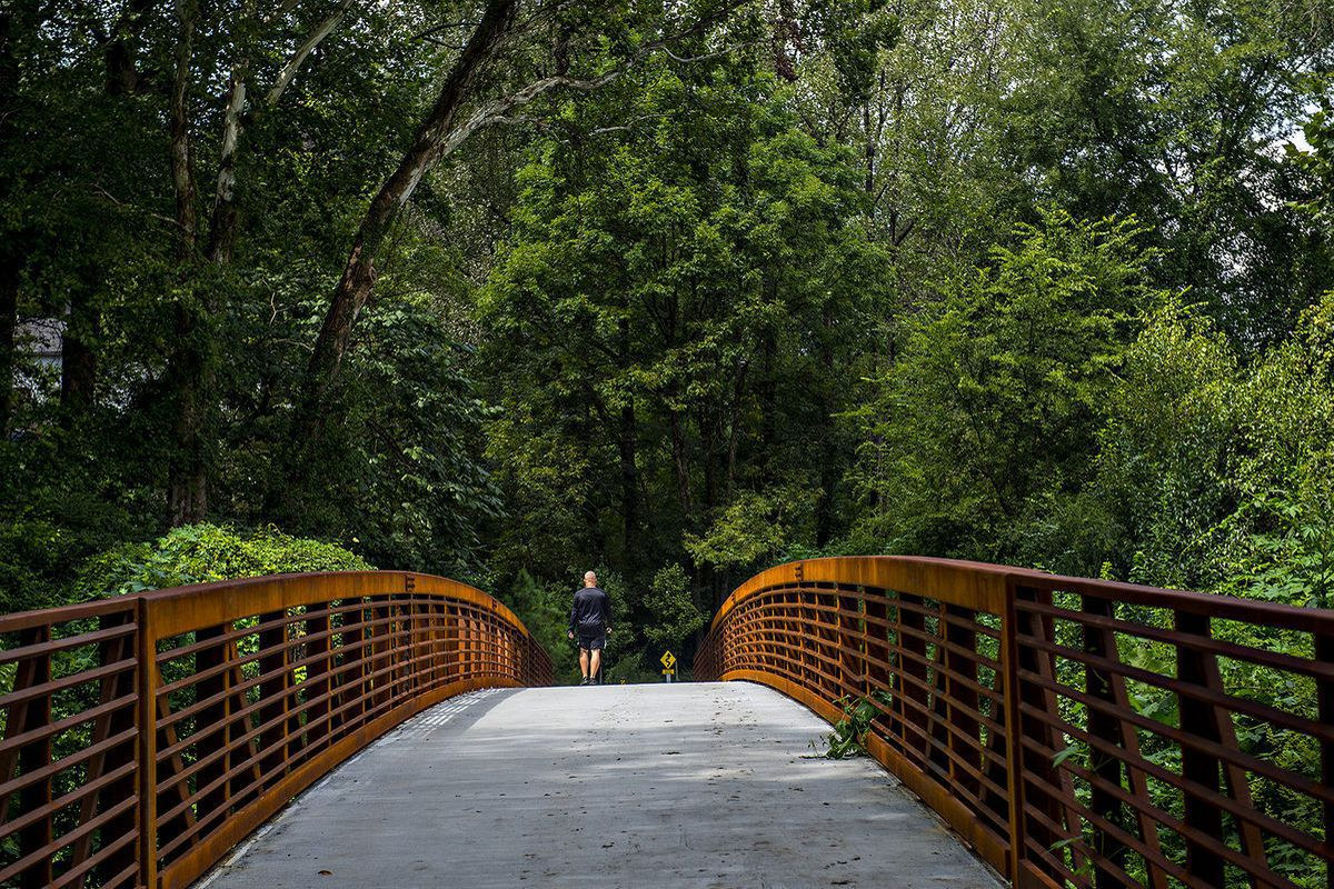 A bridge. There are two people walking on the bridge. The bridge leads to a forested area with many trees.