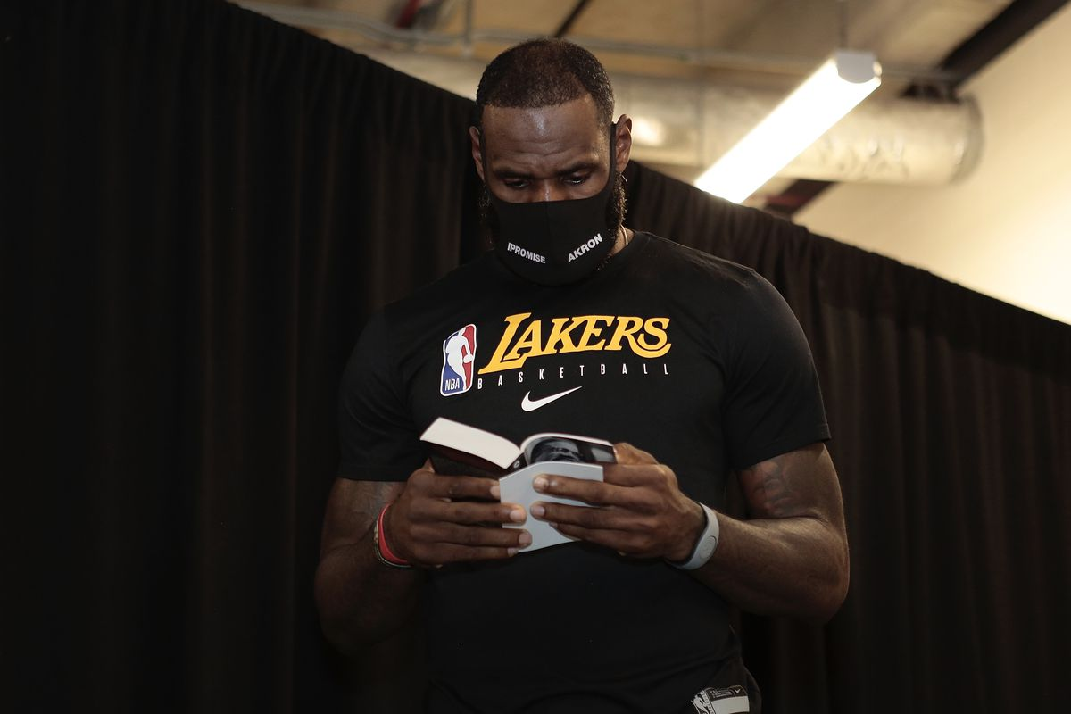 LeBron James of the Los Angeles Lakers reads a book prior to the game against the Portland Trail Blazers for Game two of the first round of the 2020 Playoffs as part of the NBA Restart 2020 on August 20, 2020 at Advent Health Arena at ESPN Wide World of Sports Complex in Orlando, Florida.