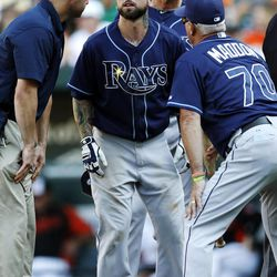 Tampa Bay Rays' Ryan Roberts, center, stands alongside manager Joe Maddon (70), third base coach Tom Foley, rear, and a member of the Rays staff after fouling a ball off his left ankle in the 11th inning of a baseball game against the Baltimore Orioles in Baltimore, Thursday, Sept. 13, 2012. Roberts left the game immediately.