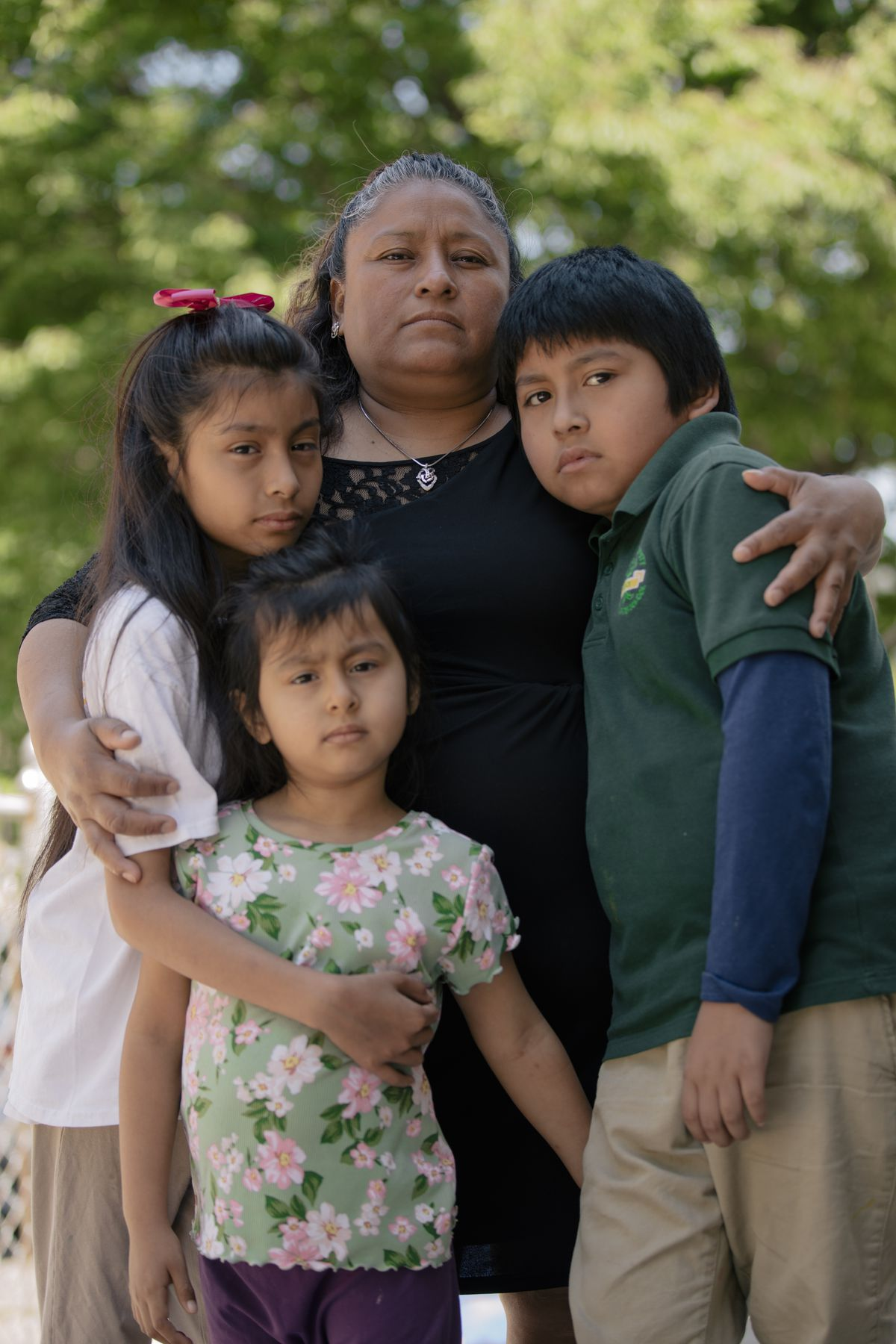 Patricia Coyotecatl (top center) holds her children (left to right) Brandy, Evelyn and Noel. Noel is wearing his green Roseville uniform.