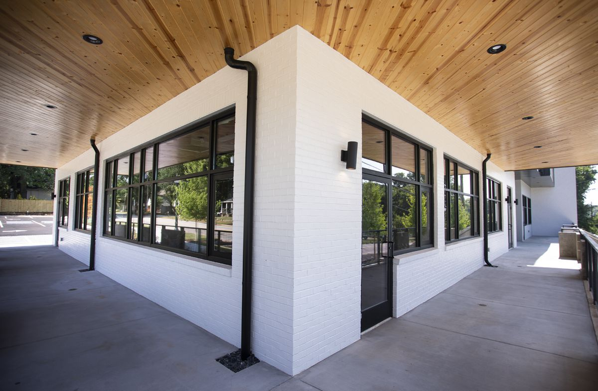 The ground floor of the office and retail building is painted white with black and wooden accents.